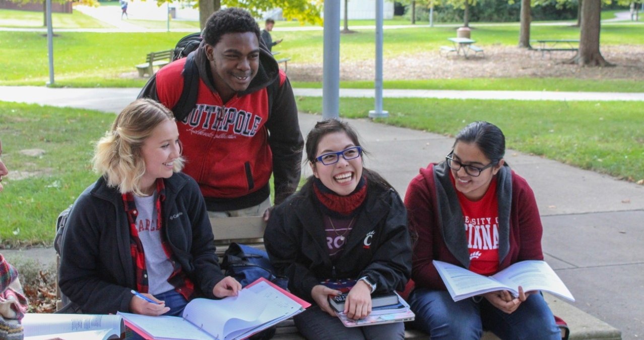 A group of students sitting on a bench at UC Blue Ash College