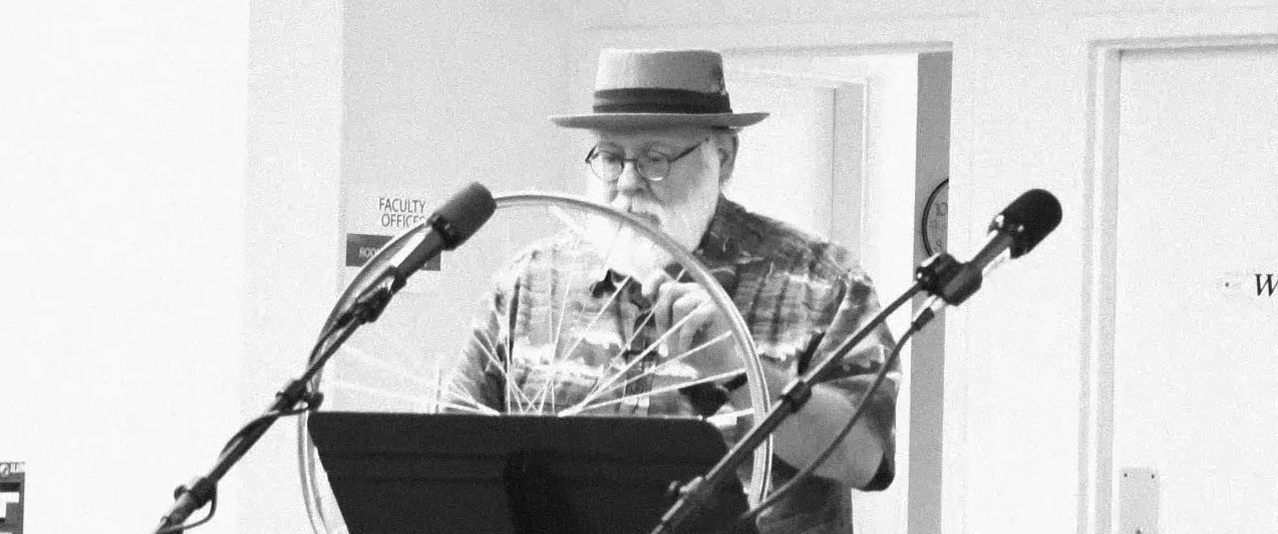 Black and white image of Mike Sanders standing in front of a microphone