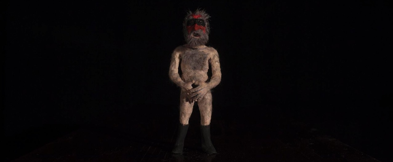 Photograph of figure standing with a black background