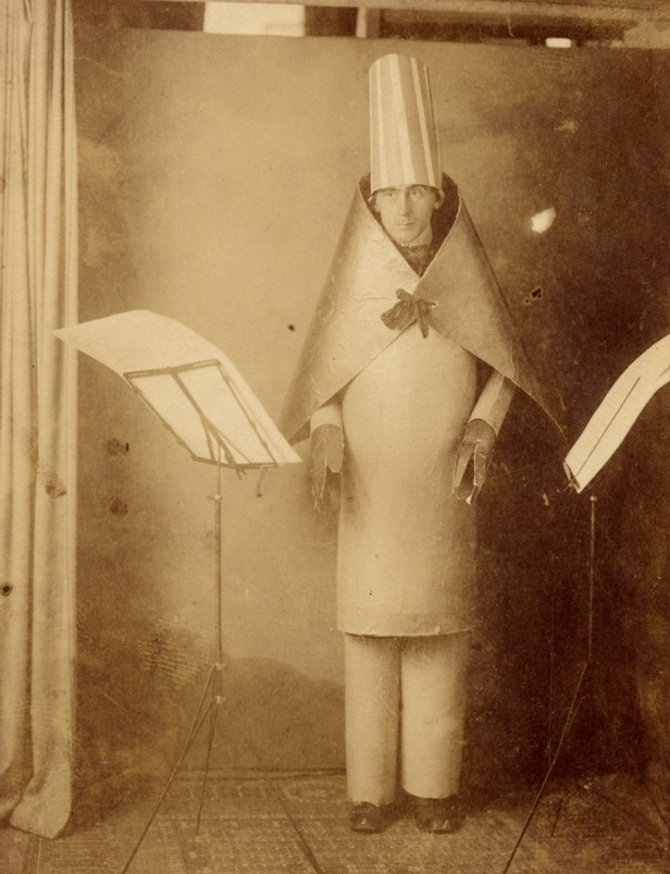 Old photo with man standing wearing a hat and cape