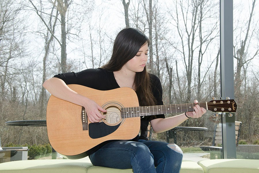 Abbigayle Richards with her guitar outside