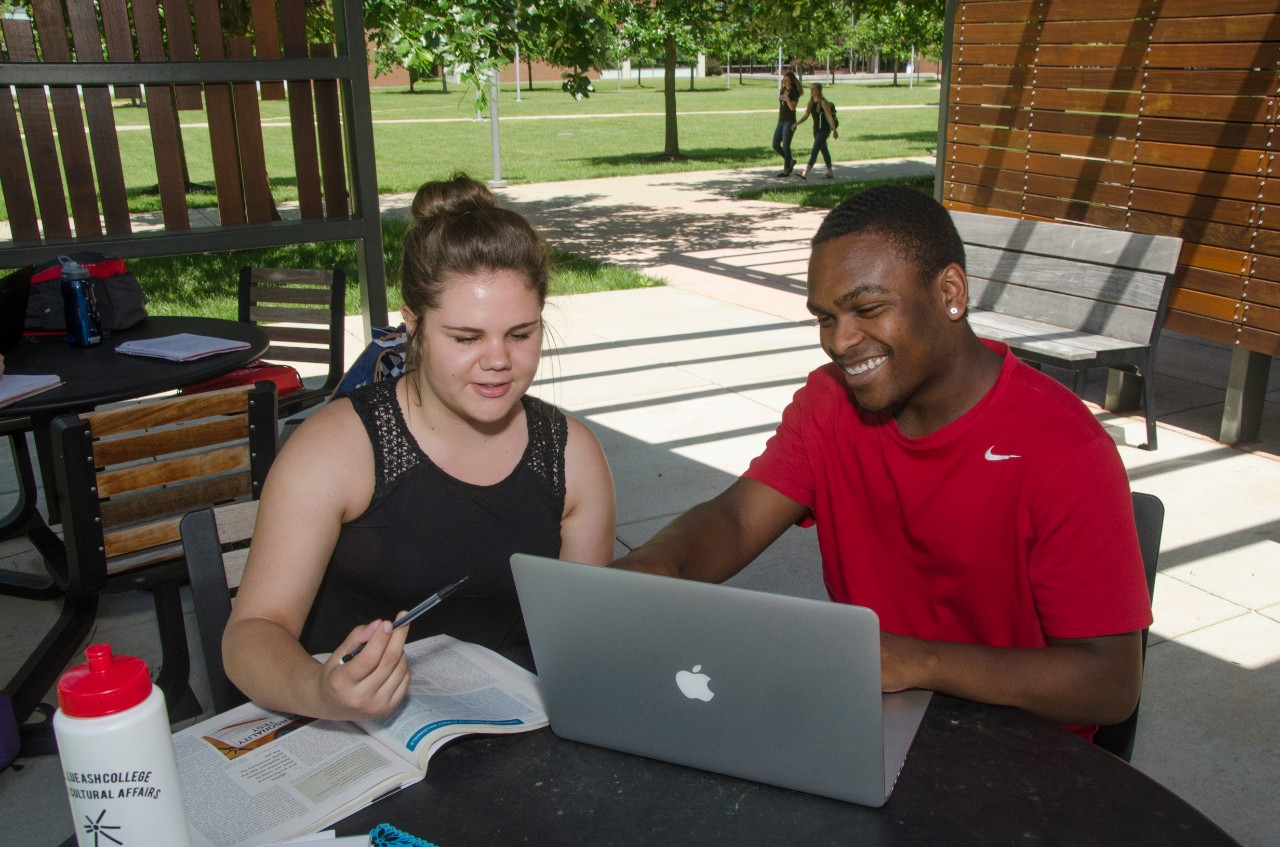 Two students working on laptop outside at UC Blue Ash College