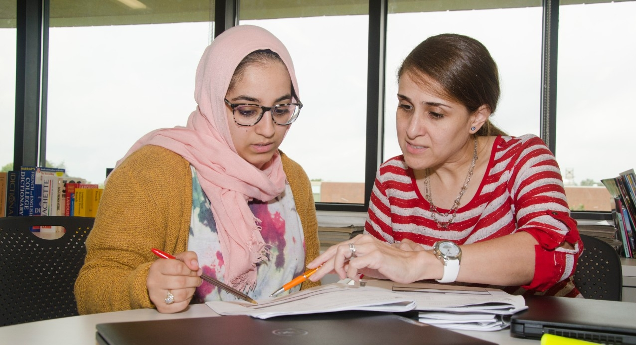 Student collaborating with professor in classroom