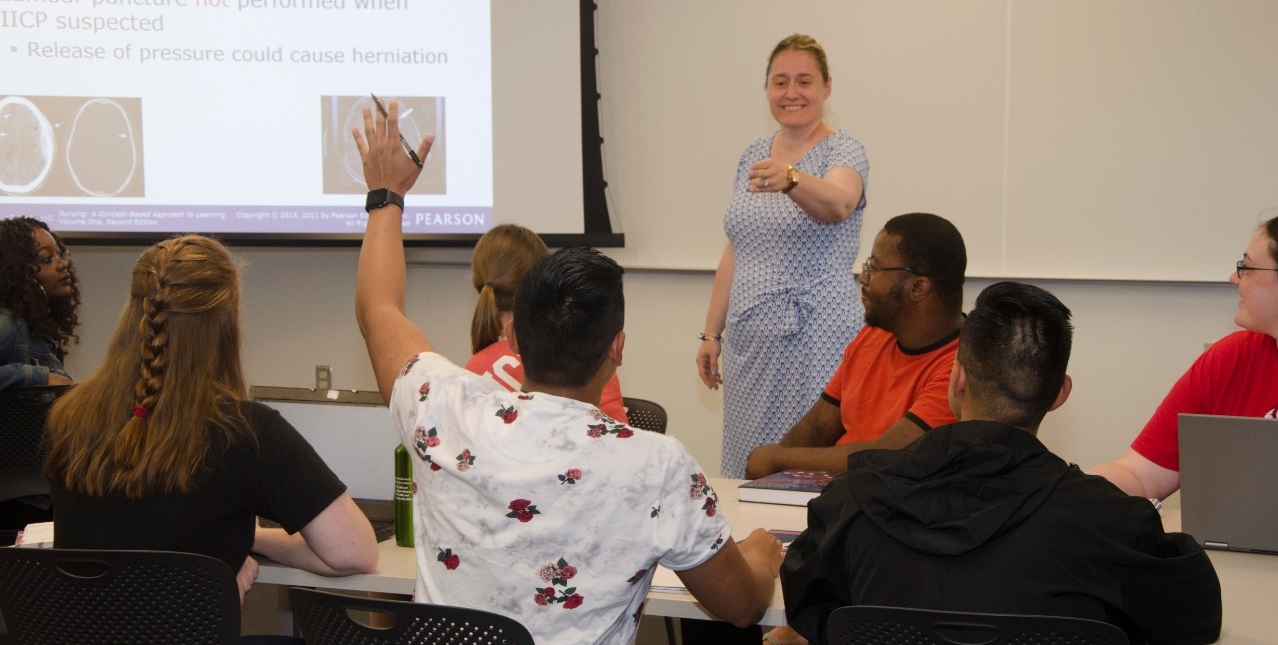 Student raising their hand in the classroom