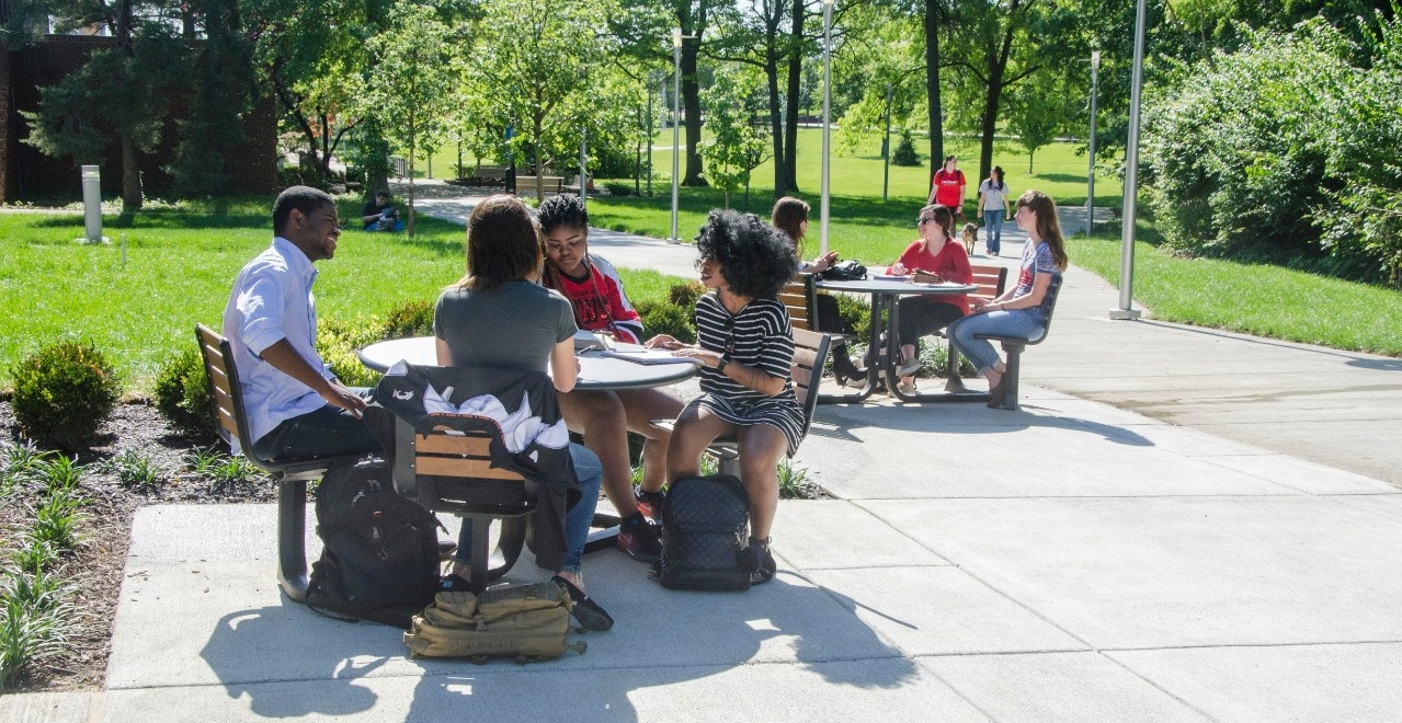 Students sitting at tables outside of Progress Hall