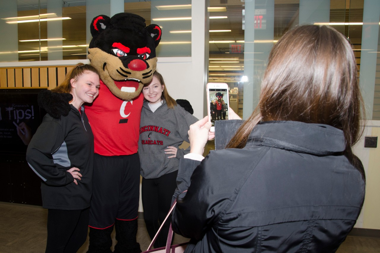Two students getting their photo taken with the UC bearcat