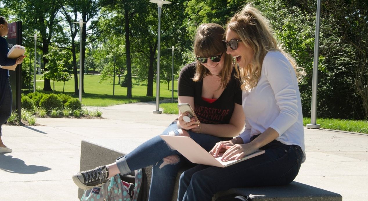 Two students sitting on bench outside at UC Blue Ash College