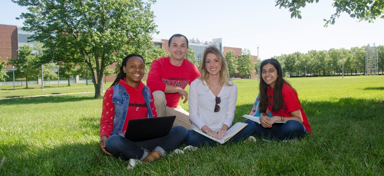 Group of students sitting in grass at UC Blue Ash College