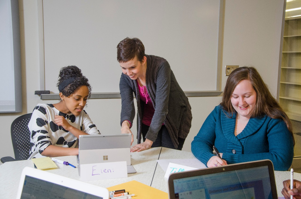 Two female students working with a library instructor