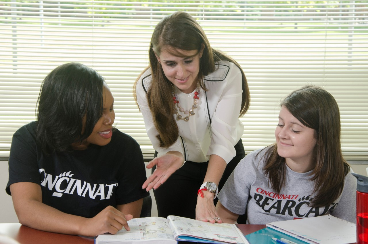 Maria Ortiz working with two students